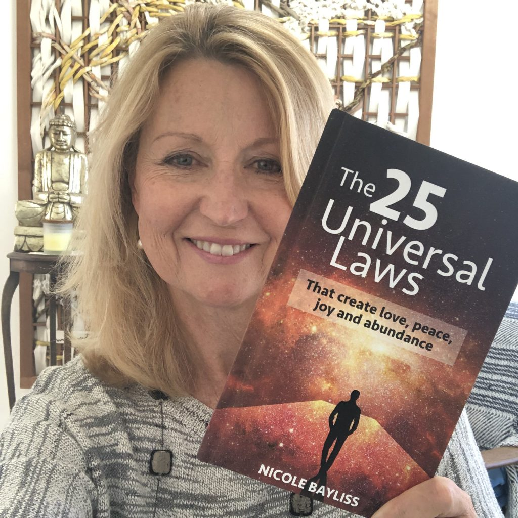 Nicole Bayliss smiling holding a copy of the book 25 Universal Laws